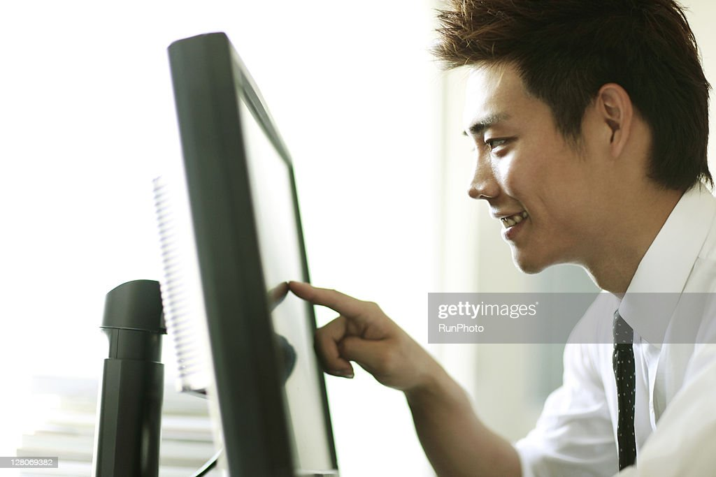 businessmen touching the monitor in the office : Stock Photo