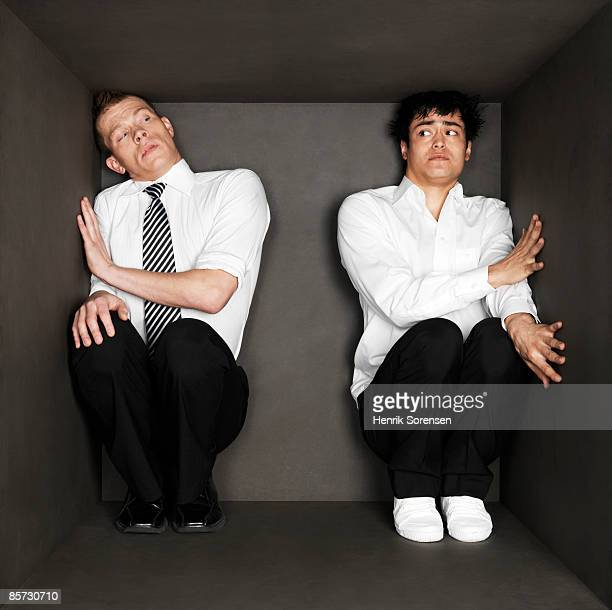 2 businessmen trapped inside a small black room