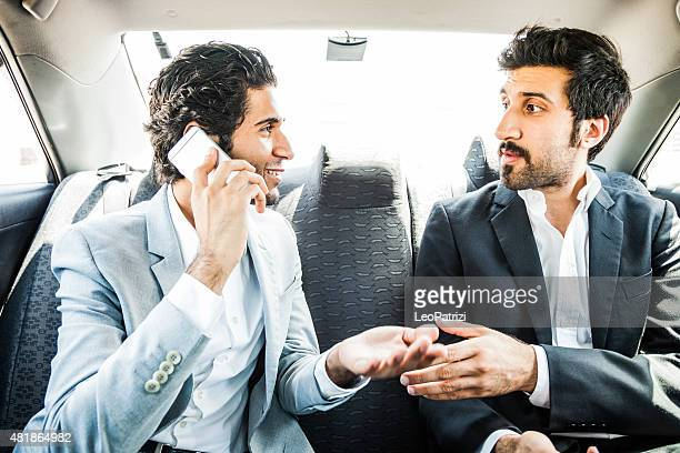 Businessmen travelling in car in middle east