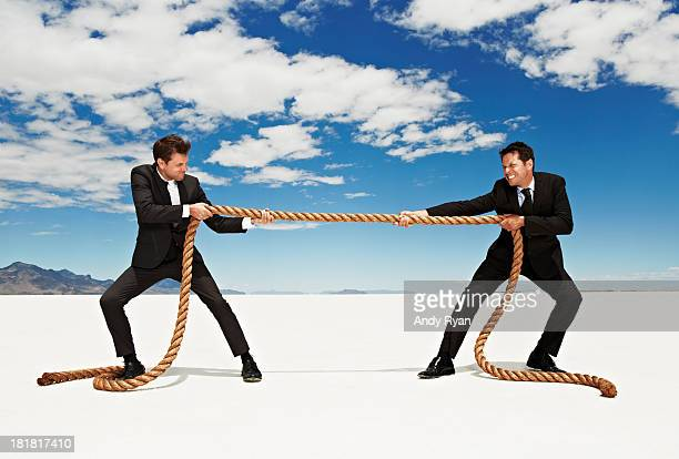 Businessmen tug o' war in desert.