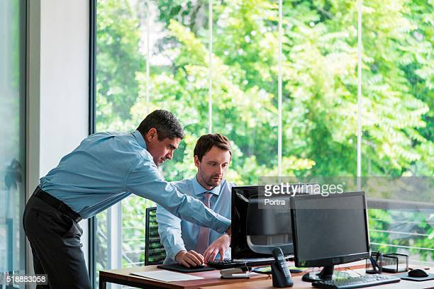Businessmen using computer at office desk