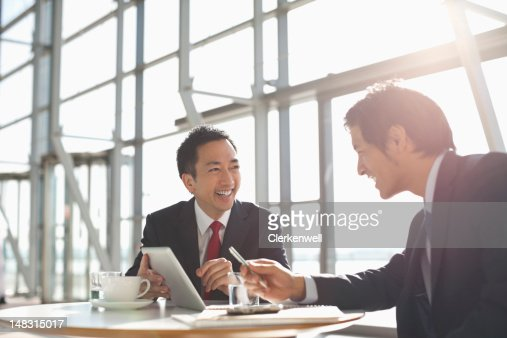 Businessmen using digital tablet in meeting