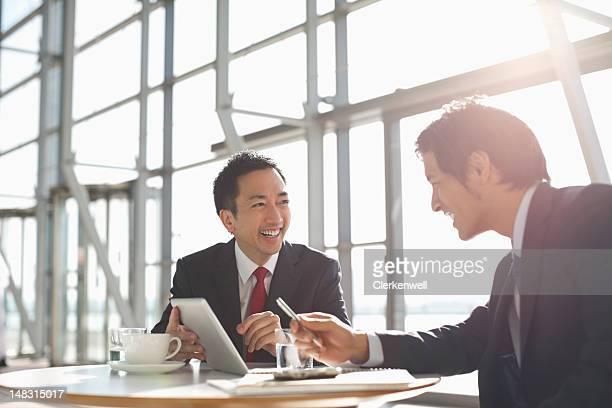 Empresarios con tableta digital en reunión