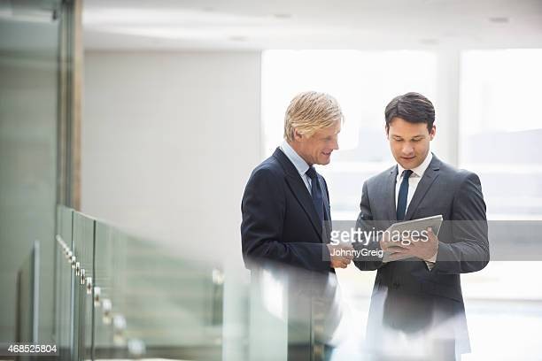 Businessmen Using Digital Tablet Together In Office