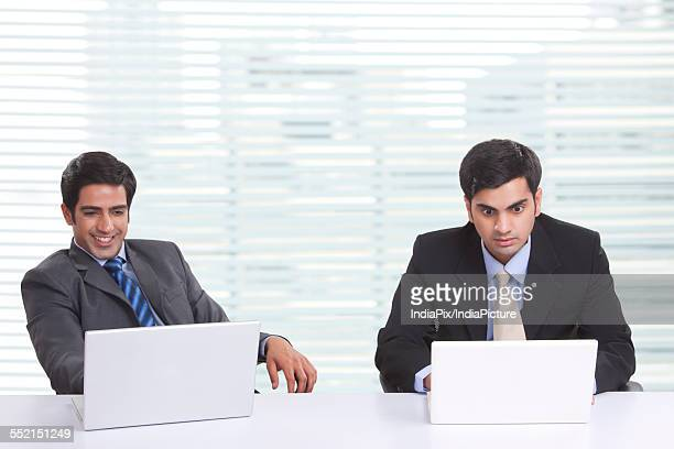 Businessmen using laptop at desk in office