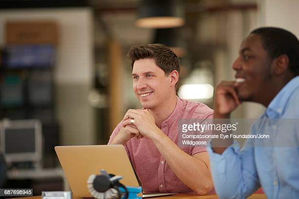 Businessmen using laptop in meeting in office