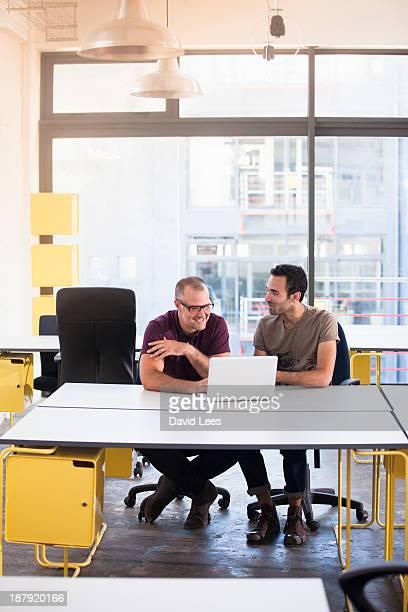 Businessmen using laptop in modern office