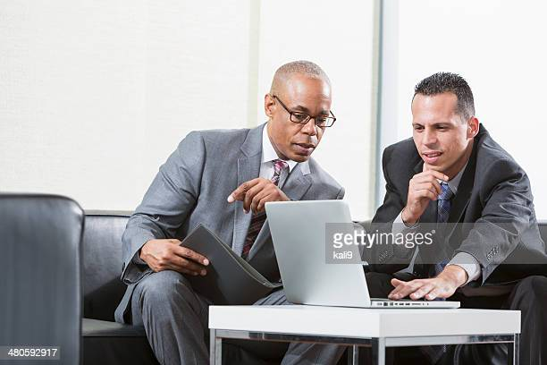 Businessmen using laptop working together on project