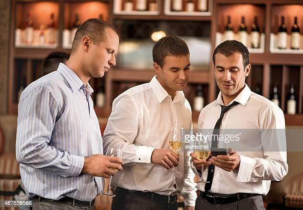 Hommes d'affaires à l'aide de smartphone en bar après une journée de travail.