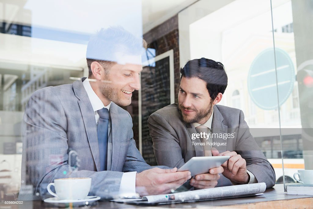 Businessmen using tablet PC in cafe : Stock Photo