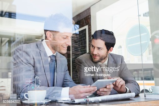 Businessmen using tablet PC in cafe : Stock-Foto