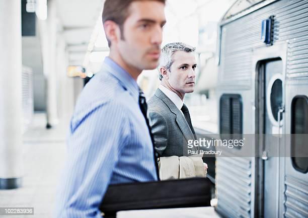 Geschäftsleute warten auf Zug im Bahnhof