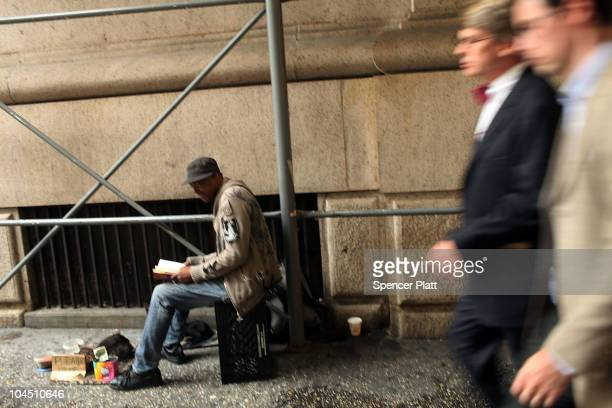 Businessmen walk by a homeless man on the street on September 28 2010 in New York City A new report released by the US Census Data shows that the...
