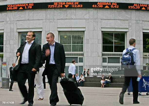 Businessmen walk in front of an electronic display showing share prices in Canary Wharf business district in east London 17 August 2007 London's FTSE...