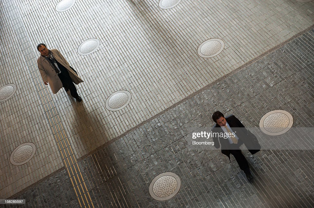 Businessmen walk inside a building in Tokyo, Japan, on Monday, Dec. 10, 2012. Japan's economy shrank in the last two quarters, meeting the textbook definition of a recession, as the dispute with China, the country's biggest export market, caused consumers there to shun Japanese products and contributed to Japan's worst year for exports since the global recession in 2009. Photographer: Noriko Hayashi/Bloomberg via Getty Images