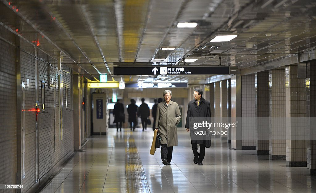 Businessmen walk on a concourse at a subway terminal in downtown Tokyo on December 28, 2012. Tokyo shares on December 28 closed at their highest point since last year's quake-tsunami, ending 2012 up almost 23 percent as Japan's new government pledges to turn around the long-suffering economy. AFP PHOTO / KAZUHIRO NOGI