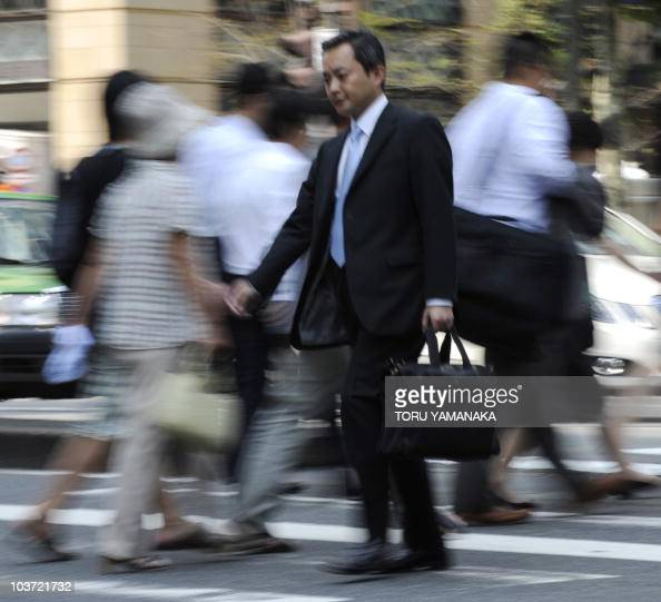 Businessmen walk on the street in downtown Tokyo on August 27 2010 Japan's unemployment rate fell to 52 percent in July dropping by 01 percentage...