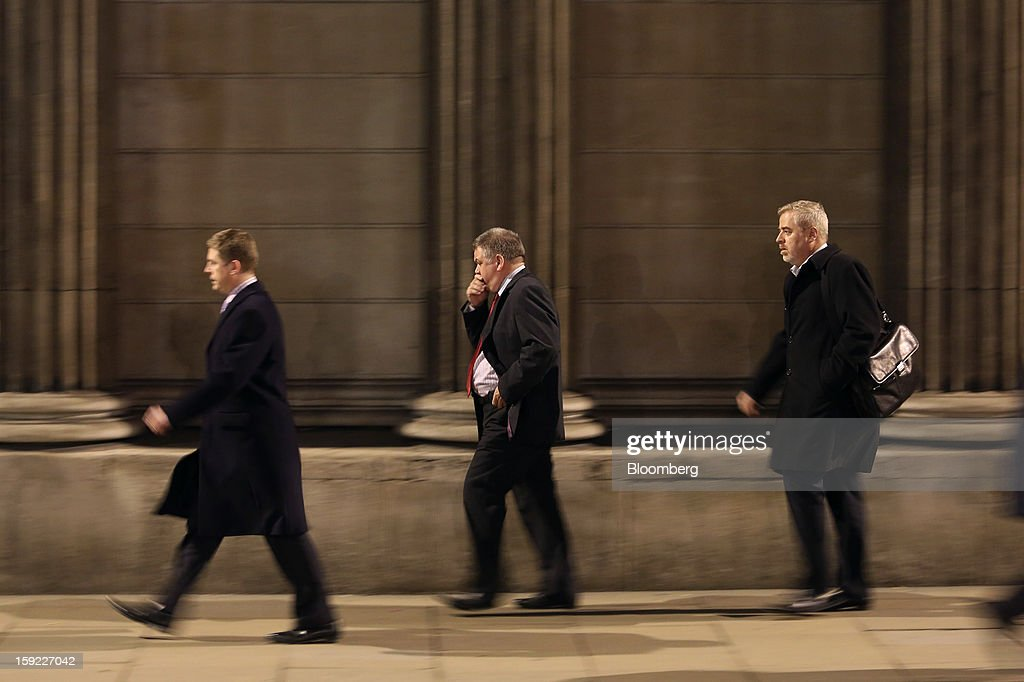 Businessmen walk past stone columns outside the Bank of England (BOE) in London, U.K., on Wednesday, Jan. 9, 2013. Bank of England policy makers will probably refrain from adding further stimulus to the U.K. economy today as their new credit-boosting program shows early signs of success. Photographer: Chris Ratcliffe/Bloomberg via Getty Images