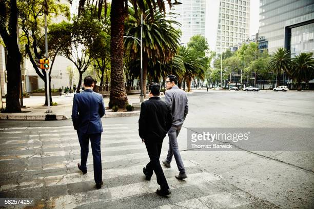 Businessmen walking across crosswalk on street