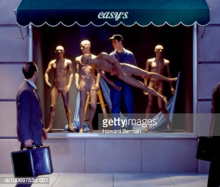 Businessmen walking by mannequins worker : Bildbanksbilder