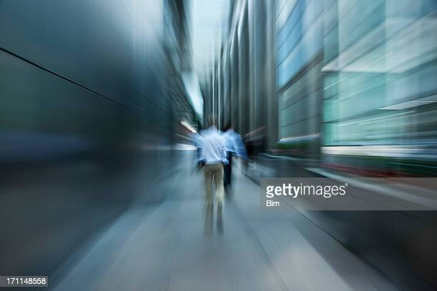 Businessmen Walking Down Futuristic Passage in Financial District