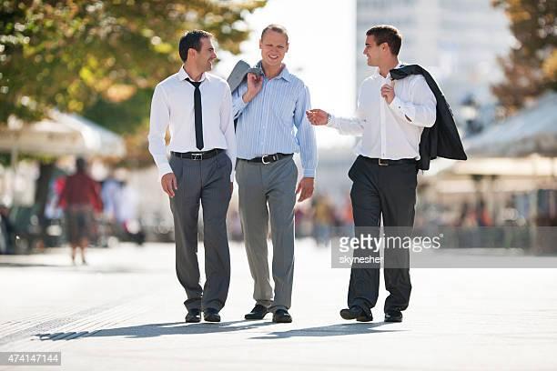 Geschäftsleute gehen auf der Straße und reden miteinander.