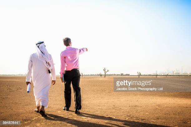 Businessmen walking in desert