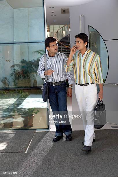 Businessmen walking in front of office entrance, one using cellphone