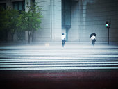 Businessmen walking in heavy rain