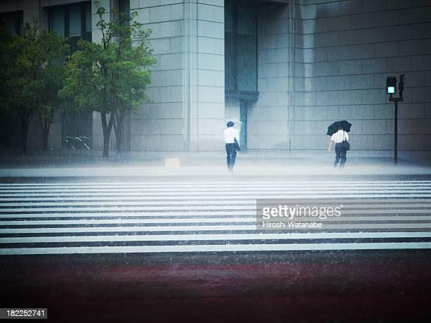 Businessmen walking in heavy rain