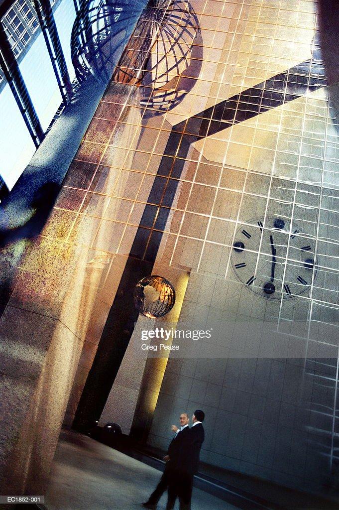 Businessmen walking in lobby,globes superimposed (Digital Composite) : Stock Photo