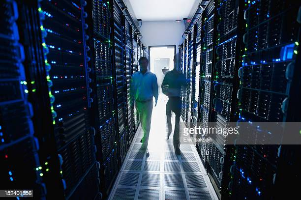 Businessmen walking in server room