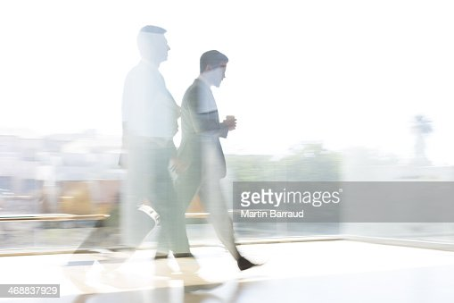 Businessmen walking in sunny airport corridor
