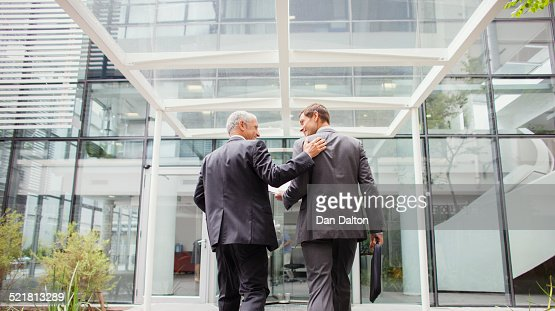 Businessmen walking into office building together