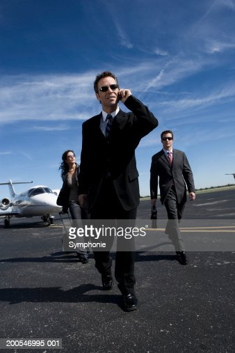 Businessmen walking on airport tarmac using mobile phone, low angle view : Stock Photo