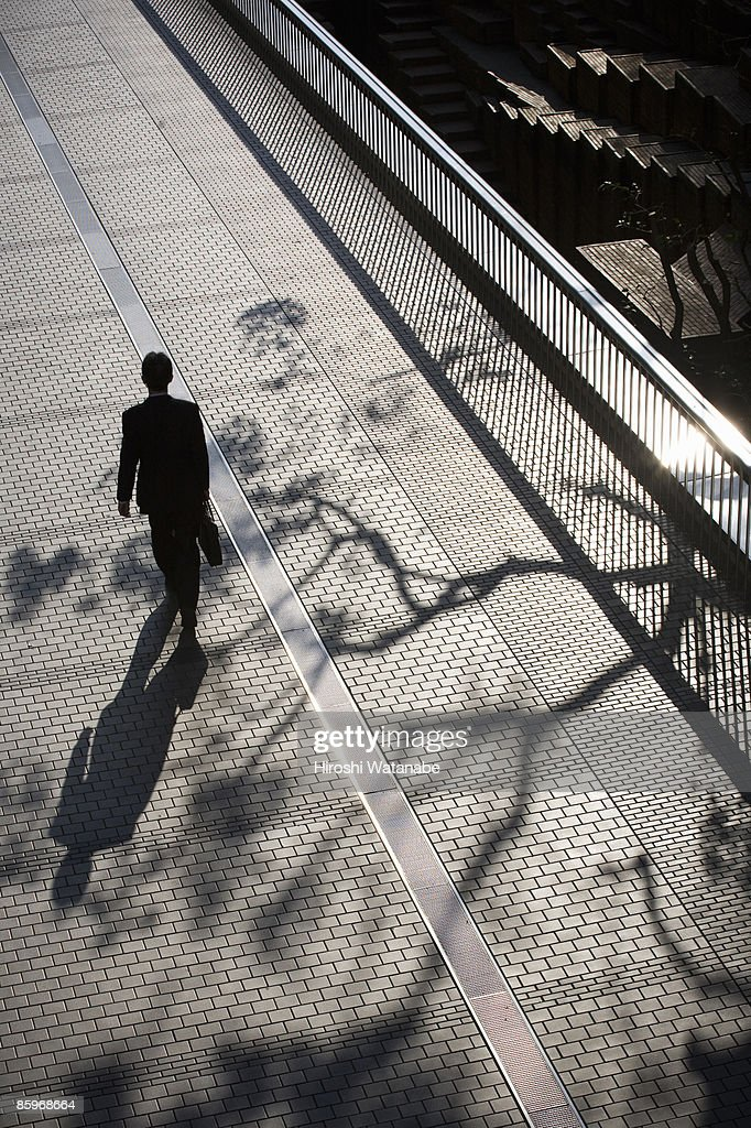 Businessmen walking on the pavement : Stock Photo