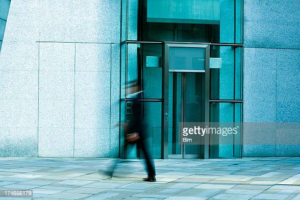 Businessmen walking past glass elevator, London, England