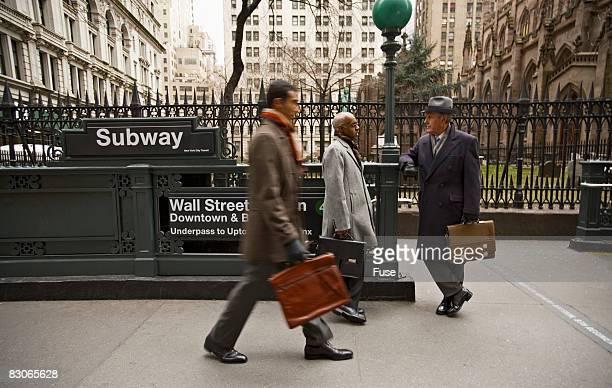Businessmen Walking Past Wall Street Station