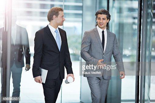Businessmen walking threw swing door : Stock Photo