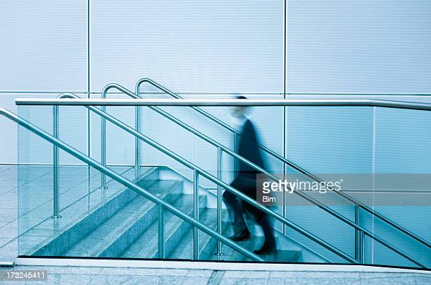Businessmen walking up stairs blue toned image
