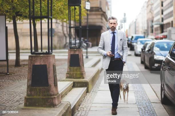 Businessmen walking with dog in city