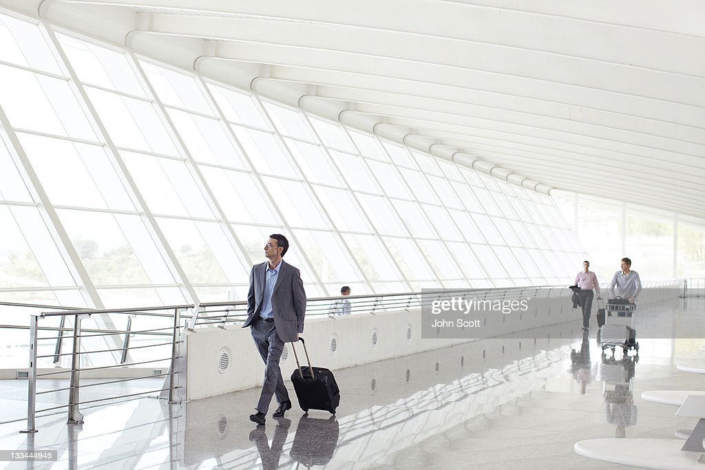 Businessmen walking with luggage at airport : Stock Photo