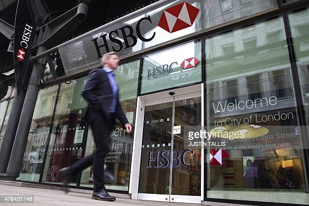 A businessmen walks past the entrance to a HSBC bank branch in London on June 9 2015 Scandalhit bank HSBC said it would cut its global headcount by...