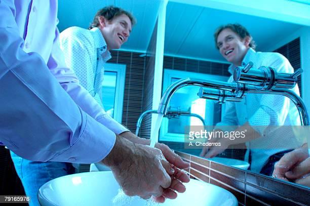 Businessmen washing hands in washroom, smiling