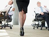 Businessmen watching sexy co-worker