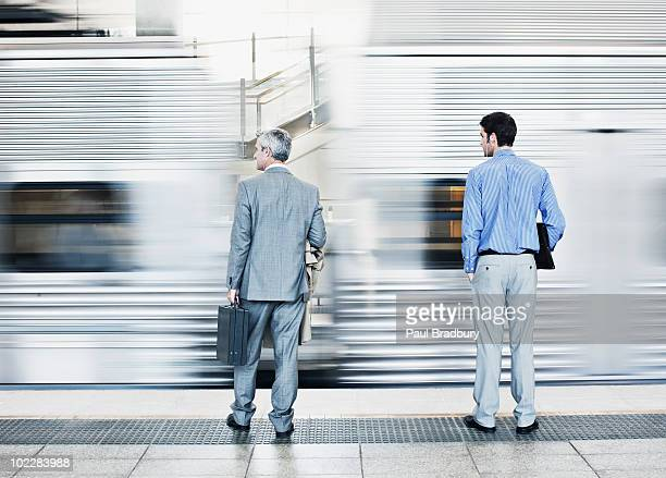 Businessmen watching speeding train