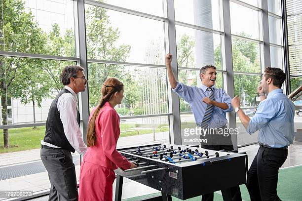 Businessmen winning at table football in lobby