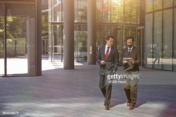 Businessmen with an iPad walking and talking
