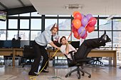 Businessmen with balloons and party hats