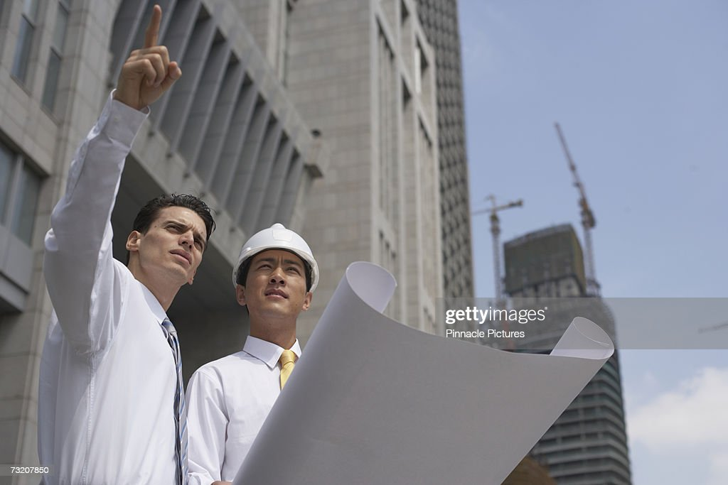 Businessmen with blueprint outdoors : Stock Photo